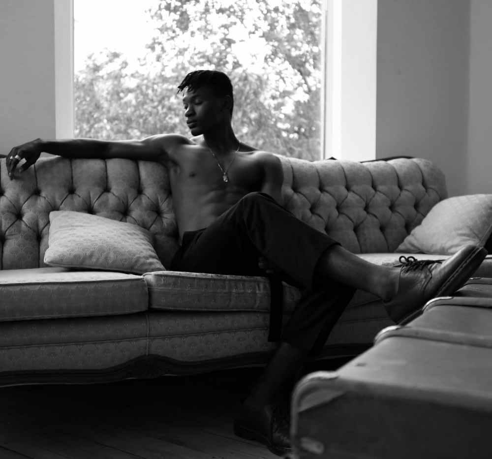 monochrome photo of man sitting on sofa