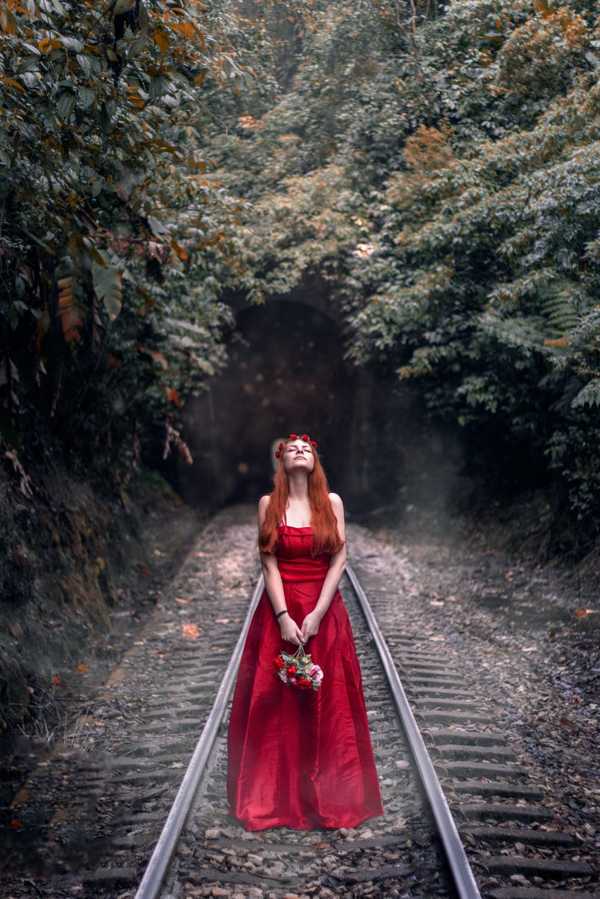 woman in red dress standing on train track